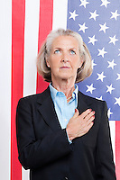 Senior businesswoman with hand over heart against American flag