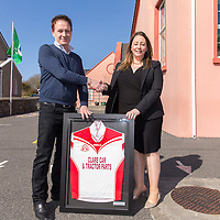 Martin O'Malley from Clare Car and Tractor Parts being presented with a framed Jersey by Principle Rosemary Corry