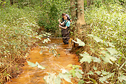 Ohio University engineering student Liz Myers (Near) and Michelle Shively, Sunday Creek Watershed Coordinator at Rural Action, take water quality samples at Sunday Creek at an acid mine drainage discharge site in Truetown, Ohio. Photo by Ben Siegel/ © Ohio University