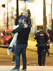 © Licensed to London News Pictures. 23/05/2017. Manchester, UK. A man lifts a girl , believed to be his daughter , as she leaves the arena . Anxious parents wait by the police cordon for news of children inside the Manchester Arena . Police and other emergency services are seen near the Manchester Arena after reports of an explosion. Police have confirmed they are responding to an incident during an Ariana Grande concert at the venue. Photo credit: Joel Goodman/LNP