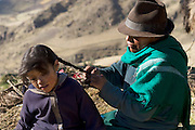 Maria Ermelinda Ayme Sichigalo, a farmer and mother of eight, fixes one of her daughters' hair outside her adobe house in Tingo village, central Andes, Ecuador. (Maria Ermelinda Ayme Sichigalo is featured in the book What I Eat: Around the World in 80 Diets.) The caloric value of her typical day's worth of food in the month of September was 3800 kcals. She is 37 years of age; 5 feet, 3 inches tall and 119 pounds. With no tables or chairs or stove, Ermelinda cooks all the family's meals while kneeling over the hearth on the earthen floor, tending an open fire of sticks and straw. Guinea pigs that skitter about looking for scraps or spilled grain will eventually end up on the fire themselves when the family eats them for a holiday treat. Because there is no chimney, the beams and thatch roof are blackened by smoke. Unvented smoke from cooking fires accounts for a high level of respiratory disease and, in one study in rural Ecuador, was accountable for half of infant mortality.  MODEL RELEASED.