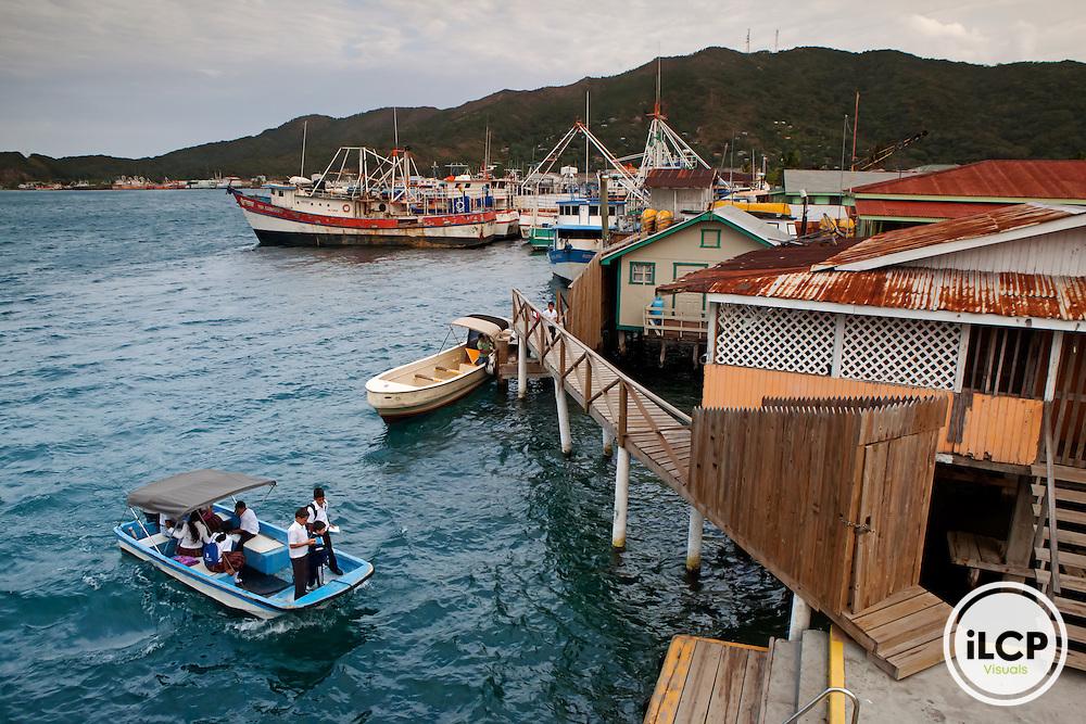 Children arriving to Bonacca for school, houses on stilts and fishing fleet, Bonacca Cay, Guanaja Island, Bay Islands, Honduras, April