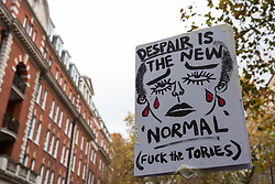 London, UK. 4th November, 2015. A placard critical of the Government is held high among thousands of students attending a National Demonstration for a Free Education. The demonstration was organised by the National Campaign Against Fees and Cuts (NCAFC) in protest against tuition fees and the Government's plans to axe maintenance grants with effect from 2016.