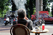 man smoking on a outdoors cafe terrace Amsterdam