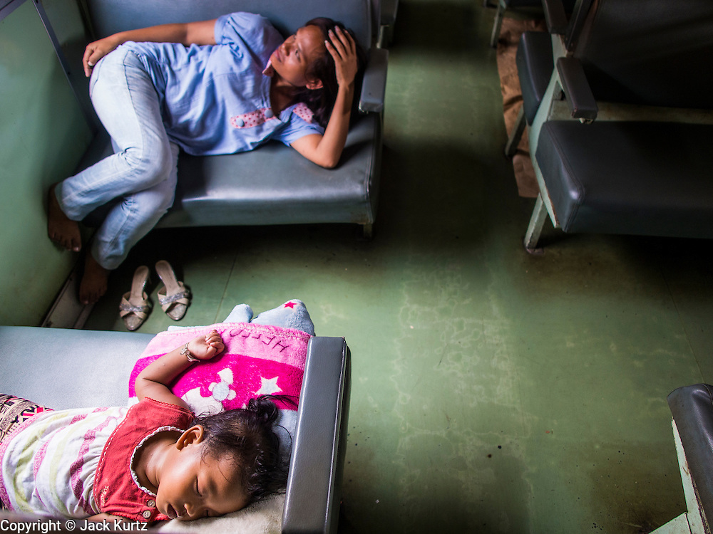 16 APRIL 2014 - BANGKOK, THAILAND: A girl and her mother sleep on their southbound train in Bangkok. They were on a train headed for Sungai Kolok in southern Thailand after coming to Bangkok for the Songkran holiday. Thai highways, trains and buses were packed Wednesday as Thais started returning home after the long Songkran break. Songkran is normally three days long but this year many Thais had at least an extra day off because the holiday started on Sunday, so many Thais started traveling on Friday of last week.    PHOTO BY JACK KURTZ