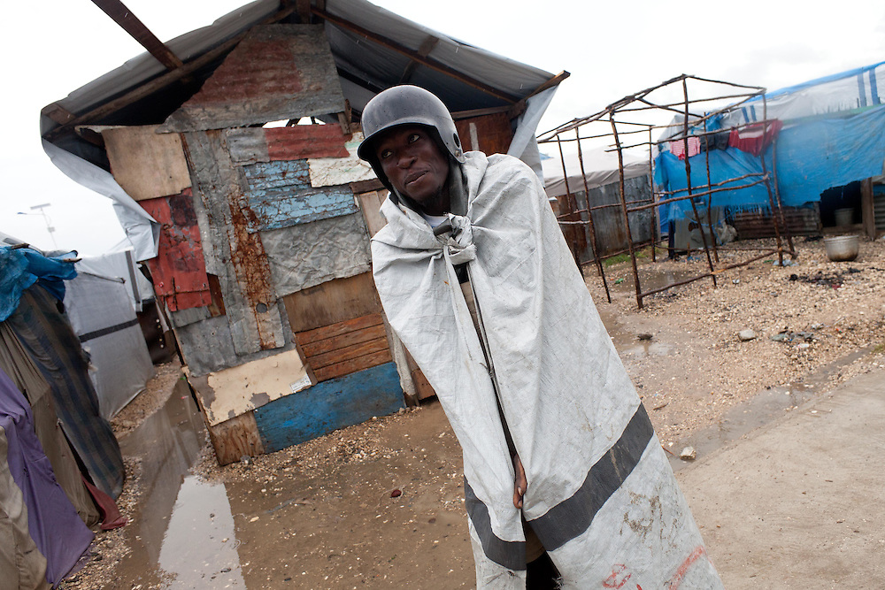 A camp resident wears a tarp and a baseball helmet to stay dry during wind and rain from hurricane Tomas.
