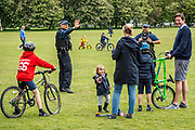 A family talk amiably to a pair of Authorised Firearms officers (AFO) who are patrolling the common reminding people of the government guidance - Clapham Common is generally quiet again as it is cooler. The 'lockdown' continues for the Coronavirus (Covid 19) outbreak in London.
