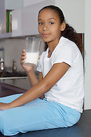 Girl (7-9) drinking milk, indoors, portrait
