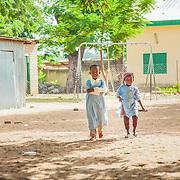 LÉGENDE: Deux enfants se dirigent vers les autres enfants qui jouent. LIEU: Centre Social Jardin d'enfants, Sarh, Tchad. PERSONNE(S): Les enfants.