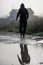 © Licensed to London News Pictures. 23/10/2016. Calais, France. A young migrant man walks in front of the church at the camp, act sunrise. Daily life continues as preparations begin for the demolition of the migrant camp in Calais, France, known as the 'Jungle'. French authorities have given an eviction order to thousands of refugees and migrants living at the makeshift living area of the French coast. Photo credit: Ben Cawthra/LNP