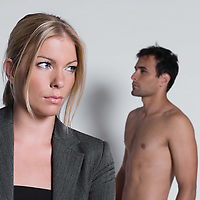sullen young couple with man naked in studio on isolated grey background