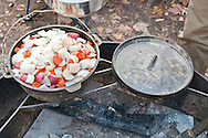 Cast iron Dutch oven cooking a beef roast and vegetables with charcoal briquets.