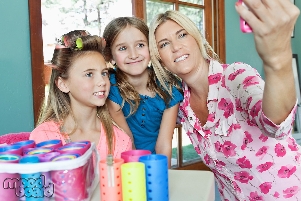 Mother with daughters taking self portrait with cell phone