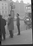 Peter Hughes in Guard Uniform.   B269..1960..06.01.1960..01.06.1960..6th January 1960..Pictured strolling through Dublin was Mr Peter Hughes resplendent in his Guards Uniform...Peter is pictured checking the bus timetable outside Clerys department store on O'Connell Street, Dublin.