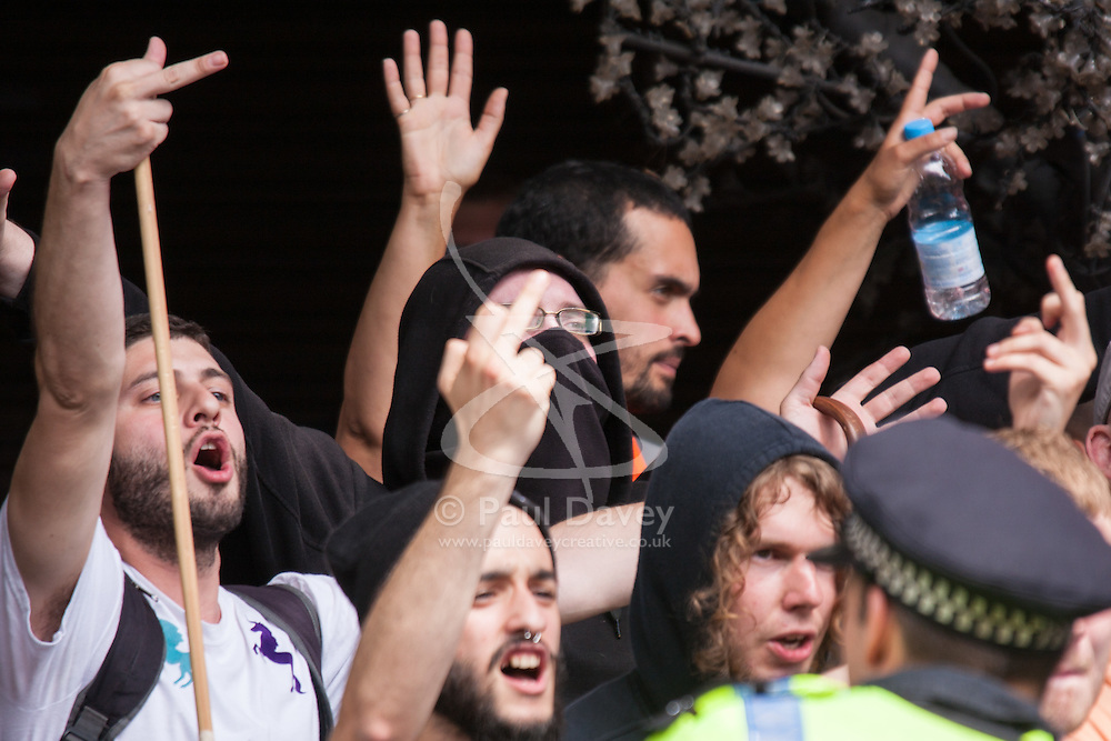 Cricklewood, London, July 19th 2014. Anti-fascists trade obscene gestures with a small number of anti-Islamists demonstrating outside the London offices of Egypt's Muslim Brotherhood.