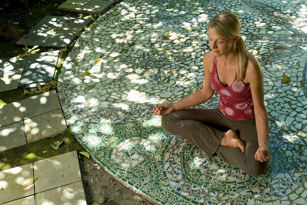 Wellness image of young woman meditating on mosaic patio