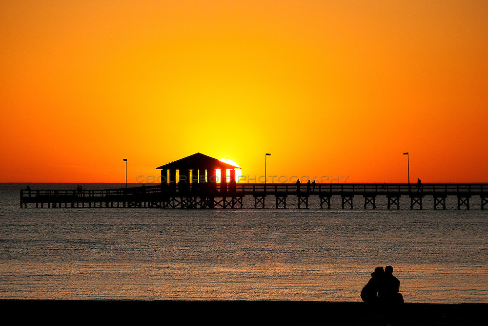 Two lovers sit on the Biloxi beach near the lighthouse pier watching the New Year's sunset in a tight embrace and kiss.  Moments later he proposed.