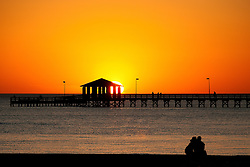 Lovers sit on the Biloxi beach near the lighthouse pier watching the sunset in a tight embrace and kiss.  Moments later he proposed.