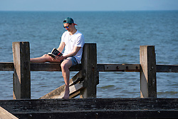 Portobello, Scotland, UK. 25 April 2020. Views of people outdoors on Saturday afternoon on the beach and promenade at Portobello, Edinburgh. Good weather has brought more people outdoors walking and cycling. The beach appears busy with possibly a breakdown in social distancing happening later in the afternoon. Solitary man reading book sitting on wooden groyne. Iain Masterton/Alamy Live News