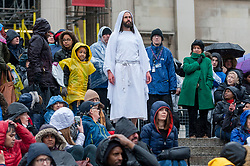 """© Licensed to London News Pictures. 30/03/2018. LONDON, UK.  Jesus, played by James Burke-Dunsmore, is resurrected after his crucifixion. The Wintershall Players present their traditional """"The Passion of Jesus"""" play in Trafalgar Square on Good Friday in front of large crowds despite the heavy rain.  The play brings to life the events leading to the crucifixion of Jesus Christ, played by James Burke-Dunsmore, and his subsequent resurrection.  Photo credit: Stephen Chung/LNP"""