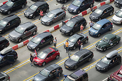 © Licensed to London News Pictures. 23/07/2016. Dover, UK.  People wait by their cars in a queue to get into the port of Dover. Long delays are currently being experienced after increased security checks were put in place. Photo credit: Peter Macdiarmid/LNP