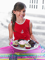 Portrait of girl (7-9) holding tray with cupcakes smiling