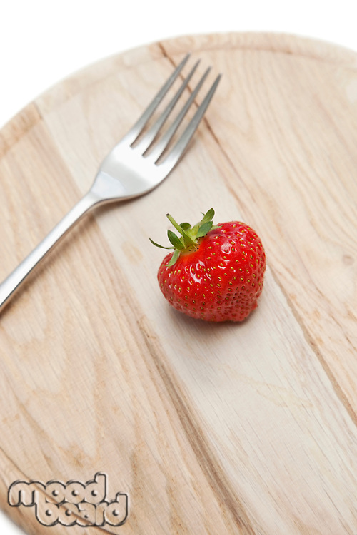 Cropped shot of wooden plate with strawberry and fork on it