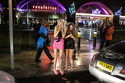 "© Licensed to London News Pictures . 22/12/2018 . Manchester , UK . Two women use their mobile phones by a taxi rank by Deansgate Locks . Revellers out in Manchester City Centre overnight during "" Mad Friday "" , named for historically being one of the busiest nights of the year for the emergency services in the UK . Photo credit : Joel Goodman/LNP"