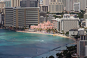 Honolulu, seen from the rim of Diamond Head Crater, an extinct volcano. Surfers in front of The Royal Hawaiian Hotel (pink, middle).