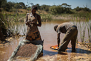 A woman is separeting cobalt from mud and rocks near a mine between Lubumbashi and Kolwezi, May 31, 2015. AFP PHOTO/FEDERICO SCOPPA