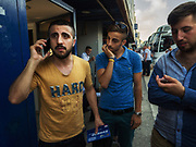 Mehmet says goodbye to relatives on the phone before boarding a bus to southern Turkey, where he will report for basic training. He hands his phone off to his younger brother and packs with him only money for the trip and one change of clothes in a shopping bag.