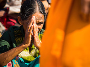 """02 JANUARY 2015 - KHLONG LUANG, PATHUM THANI, THAILAND: An Indian  woman prays as monks walk past her at Wat Phra Dhammakaya on the first day of the 4th annual Dhammachai Dhutanaga (a dhutanga is a """"wandering"""" and translated as pilgrimage). More than 1,100 monks are participating in a 450 kilometer (280 miles) long pilgrimage, which is going through six provinces in central Thailand. The purpose of the pilgrimage is to pay homage to the Buddha, preserve Buddhist culture, welcome the new year, and """"develop virtuous Buddhist youth leaders."""" Wat Phra Dhammakaya is the largest Buddhist temple in Thailand and the center of the Dhammakaya movement, a Buddhist sect founded in the 1970s.   PHOTO BY JACK KURTZ"""