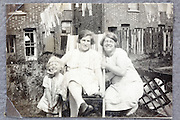 mother little child and friend posing casual in backyard 1900s England
