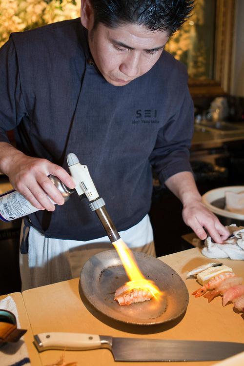 Chef Noriaki Yasutake roasts a piece of sushi.