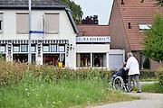 Nederland, Oeffelt, 27-6-2014 Een oudere vrouw duwt een rolstoel waar een hoogbejaarde vrouw in zit.Ze willen een straat in het dorp oversteken. Foto: Flip Franssen