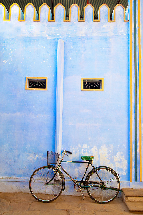 Vintage Bicycle with Basket Waiting in Front of A Blue Temple in Varanasi, India