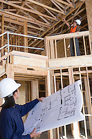 Architect and construction worker examining half constructed house