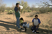 Undocumented migrants, who crossed illegally in to Arizona from Mexico, drink water from bottles placed by Rev. Mike Wilson along trail heads in the Sonoran Desert on the Tohono O'odham Nation along the deadliest stretch of the U.S./Mexico border.  One woman, (center), vomited water, a sign of heat exhaustion and dehydration.  The three were about 18 miles north of the border.
