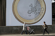 A mother and child walk past a giant Euro coin, an artwork by Danish artists Superflex, hanging from the hayward Gallery on Waterloo Bridge, on 3rd February 2017, London, England. For the third Waterloo Billboard Commission, the work is a euro coin with its value conspicuously absent – made by the group in 2012, in response to the Greek financial crisis – has gained new resonance since the UK's decision to leave the EU. The billboard is the third in a series of large-scale commissions by international artists, occupying the prominent billboard site next to Hayward Gallery.