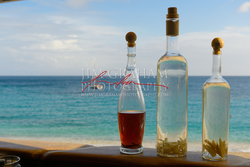 House made bottles of Rum at Do-Brazil on  Shell Beach on St Barths.   A very calm cove with a view of the islands of Statia and Saba. Count on Shell Beach to be tranquil enough for swimming and sunning.  Photography by Jim Graham