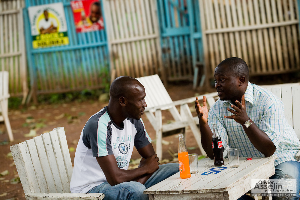 HIV/AIDS counselor Kevin Kouassi Gallet and Dr. Charles Joseph Diby discuss while sharing a drink in a bar  in Dimbokro, Cote d'Ivoire on Friday June 19, 2009.