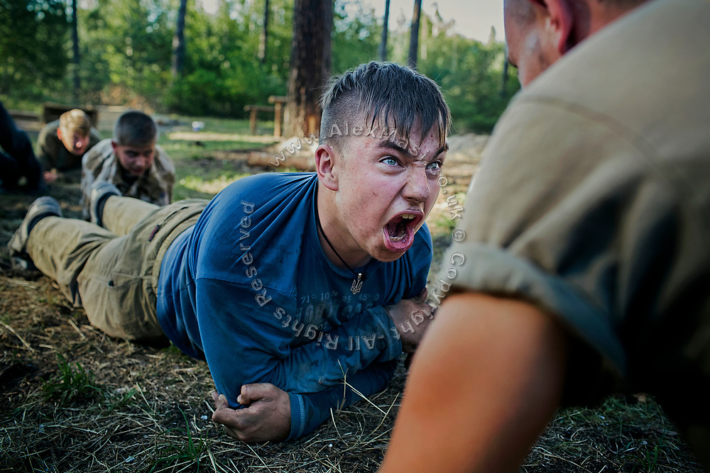 A young man participating to the ultra-nationalistic Azovets children's camp is yelling energetically while being emotionally charged by his instructor, during a tactical training in a forest near the village of Buzova, 30 km west of Kiev, the capital of Ukraine.