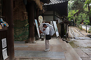 A Pilgrim, known as a Henro, prays before  he enters Ishite temple on the Shikoku 88 Temple pilgrimage, Matsuyama, Eihime, Japan.. Friday, June 26th 2015