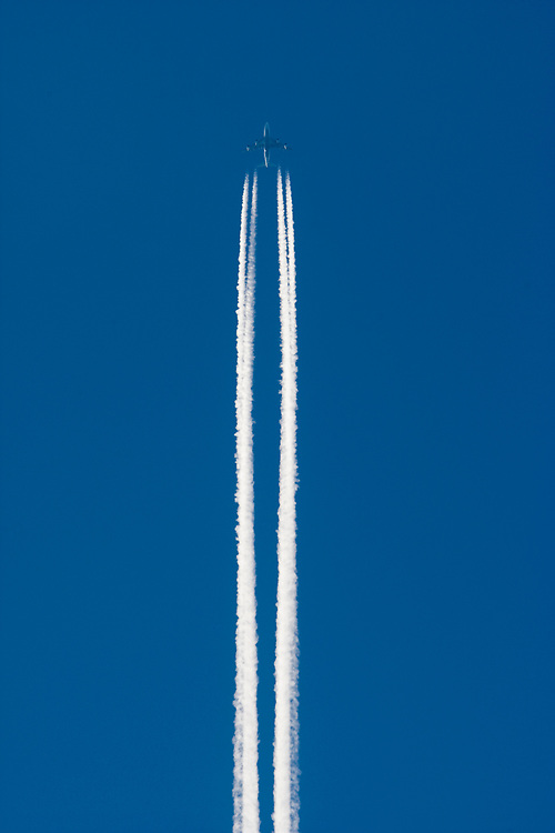 USA, Alaska, Contrail from passenger jet flying overhead at sunset