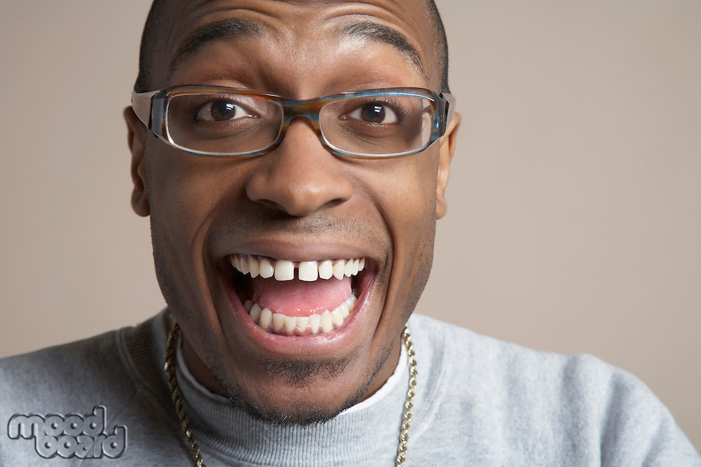 Young man laughing with mouth wide open close-up portrait
