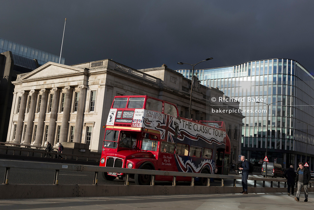 Under a heavy sky, a Classic Tour tour bus drives south to pass Fishmongers Hall and crosses London Bridge in the City of London, the capital's financial district, on 28th January 2020, in the City of London.