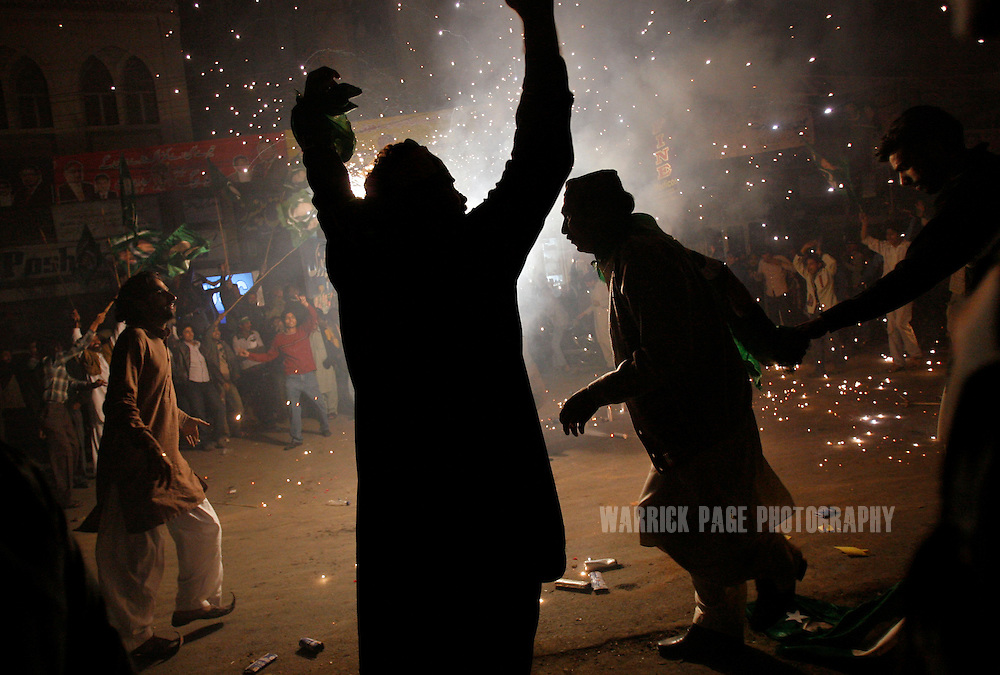 LAHORE, PAKISTAN - NOVEMBER 26: Supporters of former Prime Minister Nawaz Sharif dance around fireworks during a convoy through the city on November 26, 2007 in Lahore, Pakistan. Sharif, deposed and sent into exile eight years ago by President Pervez Musharraf, was greeted by thousands of supporters. (Photo by Warrick Page)