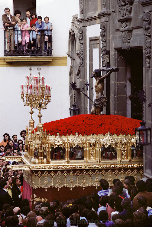A procession leaving a neighborhood church during holy week in Seville, Spain. Street processions are organized in most Spanish towns each evening, from Palm Sunday to Easter Sunday. People carry statues of saints on floats or wooden platforms, and an atmosphere of mourning can seem quite oppressive to onlookers.