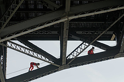 Aerial-acrobats climb the spanning beams underneath the Strawberry Mansion Bridge as they prepare for a suspended mid-air performance from the bridge during the Invisible River Festival on Saturday. (Bastiaan Slabbers/for PhillyVoice)