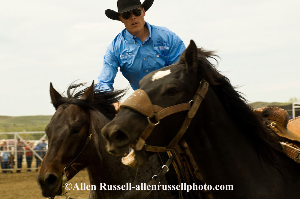 Rodeo pickup man Jay Shaw picks up saddle bronc, Miles City Bucking Horse Sale, Montana, <br /> MODEL RELEASED